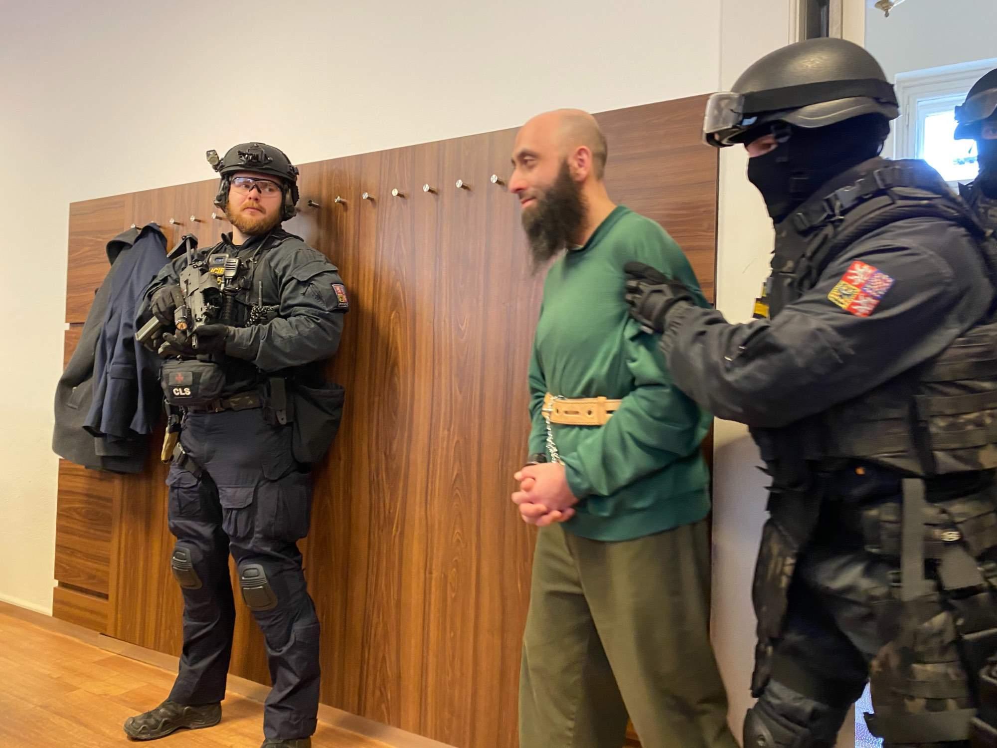 Obviněný Sámer Shehadeh přichází do soudní místnosti v doprovodu ozbrojené eskorty