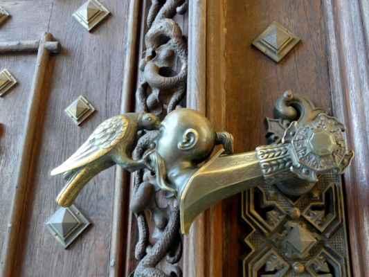 Bronzová klika zámeckých vrat krásně zobrazuje známý symbol ze Schwarzenberského znaku. Po dobytí turecké pevnosti Raab v roce 1598 Adolfem I. ze Schwarzenbergu byl v roce 1599 znak doplněn o hlavu Turka, které havran či krkavec klove oko. Raab je dnešní město Györ v Maďarsku.