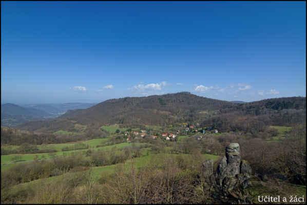 Středohoří - Skalní útvar Učitel a žáci na úbočí Holého vrchu,v pozadí ves Kundratice a Varhošť..